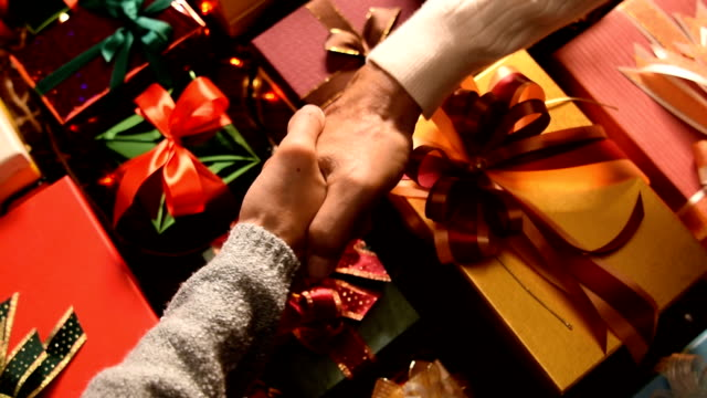 Man shake hand with woman and giving a christmas present to her