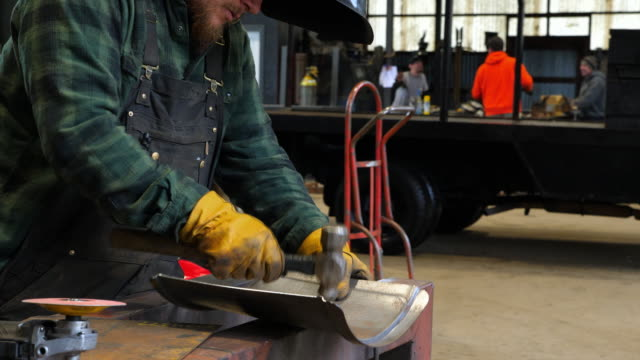 MS Man shaping metal with hammer for project in metal workshop