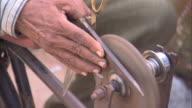 CU TU Man sharpening pair of scissors on grinding wheel, Districts of Delhi, India
