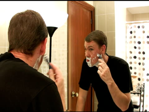 Man shaves face in front of mirror