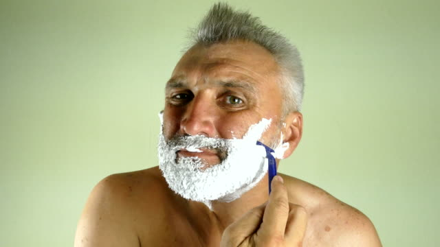man shaves with a manual razor