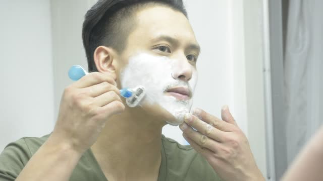 man shaving in toilet