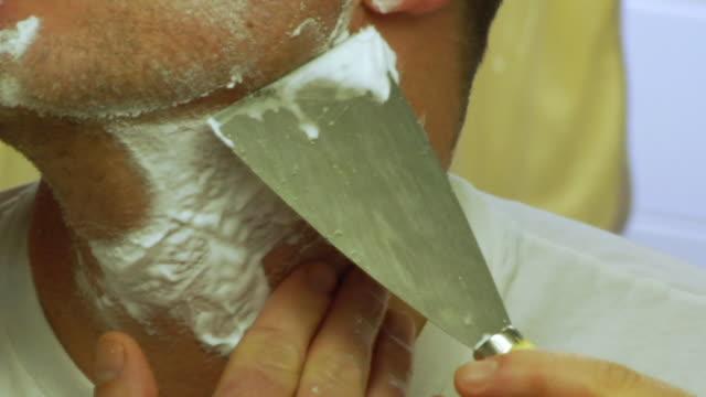 CU Man shaving with putty knife / Brooklyn, New York, USA