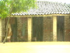 Man sheltering under porch of house as heavy rain pours down causing flooding India
