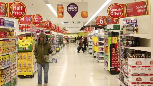 Man shopping for food in chilled meat aisle of a Tesco Plc supermarket in Kensington west London Various aisles of a Tesco supermarket with signage...