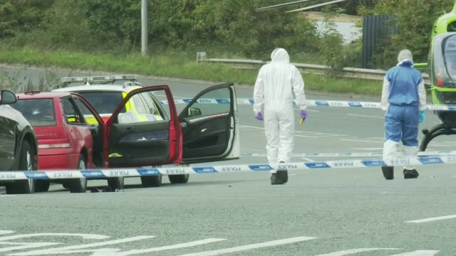 Man shot dead in armed police operation near M5 in Bristol ENGLAND Bristol EXT Forensic police in overalls searching road beside red car