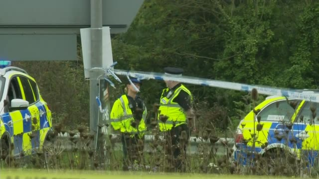 Man shot dead in armed police operation near M5 in Bristol Red car with open door as forensic officer along on road Police and tape at scene...