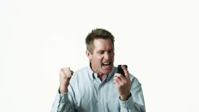 MS Man shouting during text-messaging against white background / Orem, Utah, USA