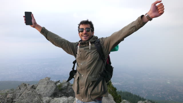 Man shouting happily after captivating the peak