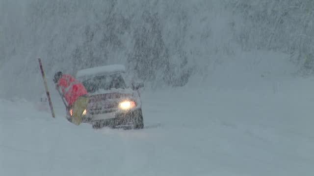 WS, Man shoveling car stacked on roadside in snowstorm, Vrhnika, Notranjska, Slovenia