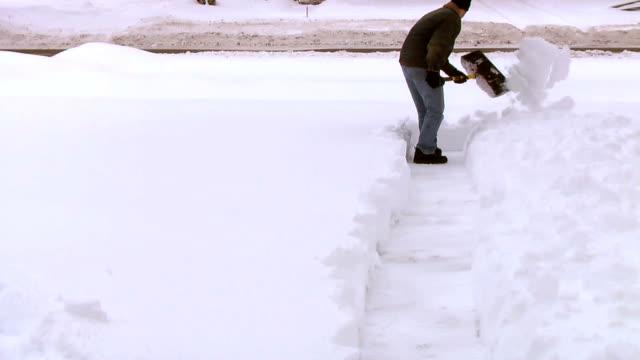 Man Shoveling Snow from Sidewalk