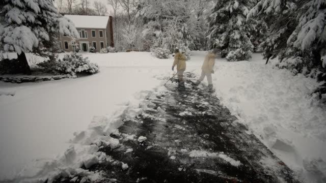 T/L, WS, Man shoveling snow on driveway, Farmington, Connecticut, USA