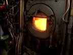 Man shovels coal into furnace on steam train Scottish Highlands