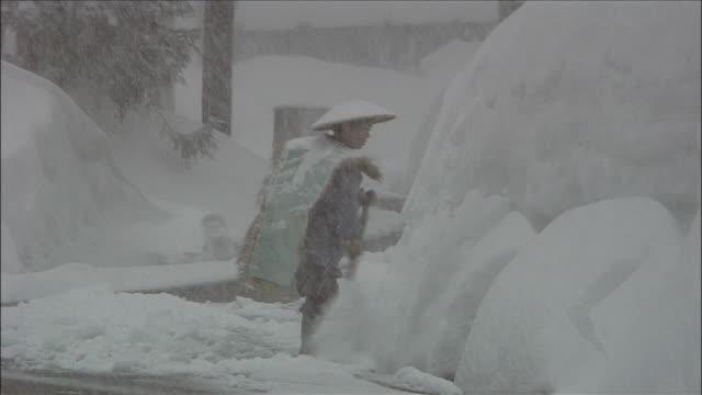 Man shovels snow from large drift as it snows heavily, Yokote, Akita, Japan