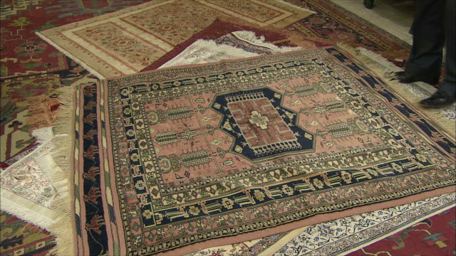 MS TU TD Man showing Persian carpets, Iran