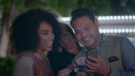 Man shows friends pictures on smartphone on night out in Las Vegas.