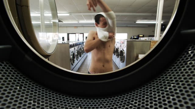 man shrinks shirt at laundromat