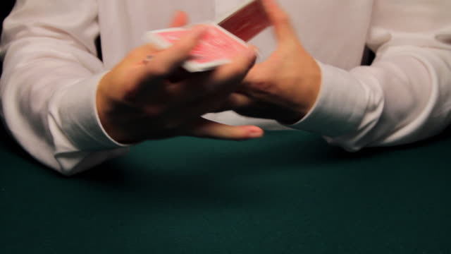 CU man shuffling and cutting deck then producing ace