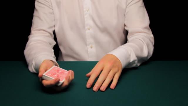MS man shuffling and cutting deck then producing four king