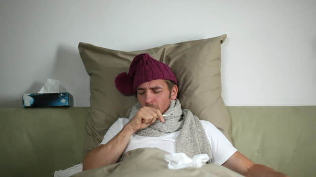 MS Man sick in bed coughing and drinking tea / Potsdam, Brandenburg, Germany