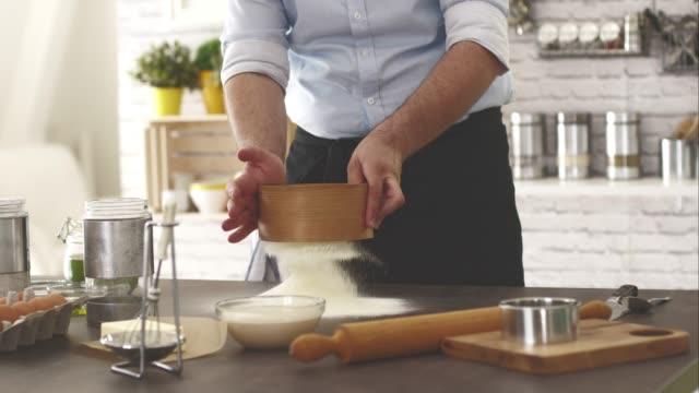 Mann siebung Mehl in der Küche