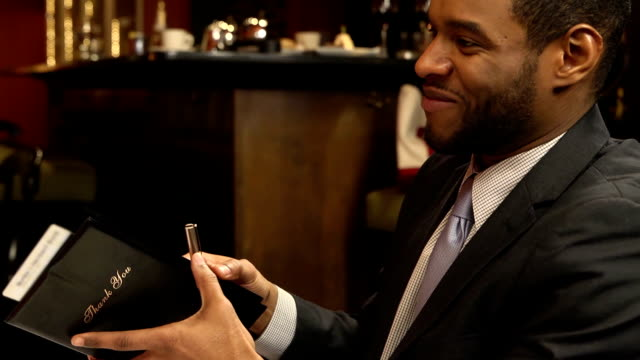 Man Signs Bill in Busy Restaurant - Close Up