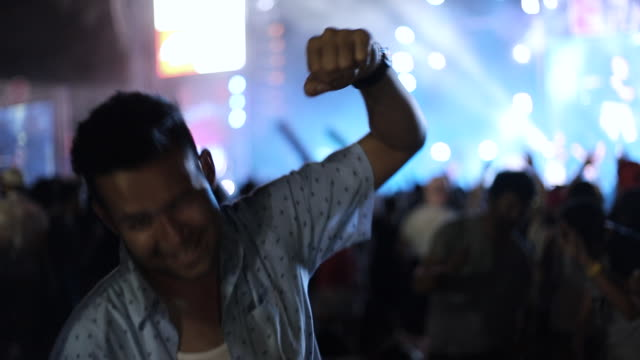 A man singing and dancing in the outdoor concert