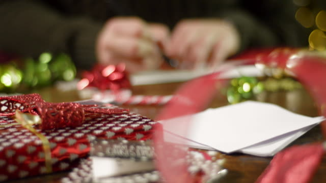 Man Sits at a Table and Writes a Christmas Card