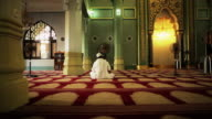 A man sits in prayer at a mosque in Singapore.