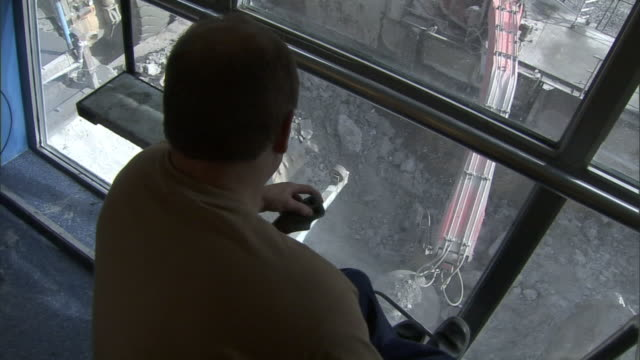 A man sits inside a cab and works the controls of a crane moving beneath him.