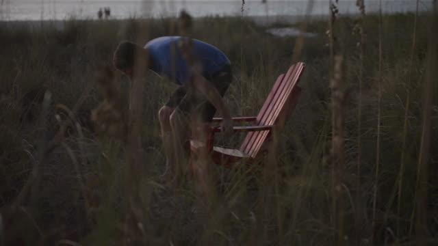 A man sits on a adirondack chair on beach