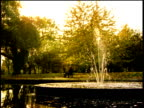 Man sits on bench in park near fountain in lake England