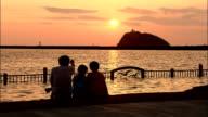 Man sits on rocks with children watching sunset, Muroran, Japan