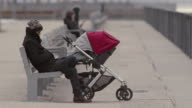 A man sits quietly with a baby sleeping in a carriage beside him.  They are at a pier park on a grey day in Brooklyn.