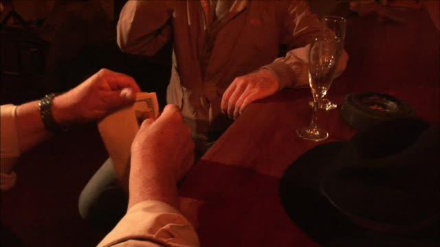 A man sitting at a bar with another patron opens an envelope full of one hundred-dollar bills.
