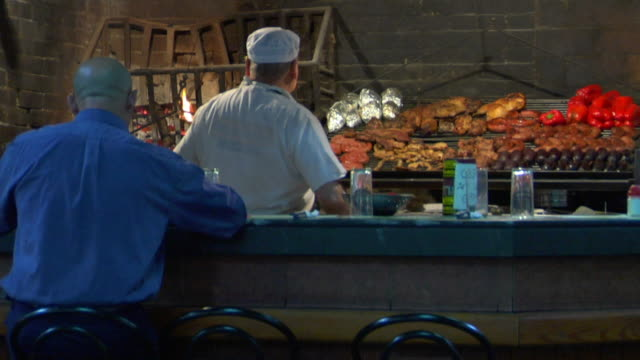 MS Man sitting at bar counter, meat on grill in background, Del Puerto Market, Montevideo, Uruguay