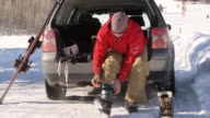 Man sitting at the back of car putting on ski boots / Ketchum, Idaho, United States