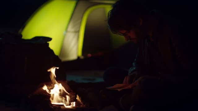 Mann sitzt im warmen Lagerfeuer Blick auf Karte