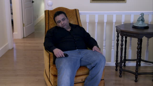 Man sitting in armchair done watching TV, stands and evaluating his weight.