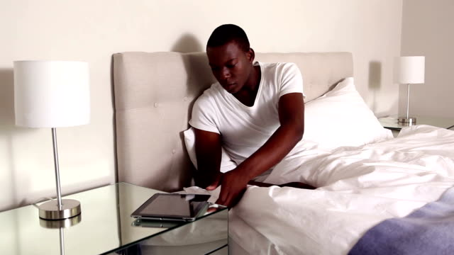 Man sitting in bed using tablet