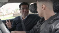 Man sitting in car with teenage son and teaching him driving