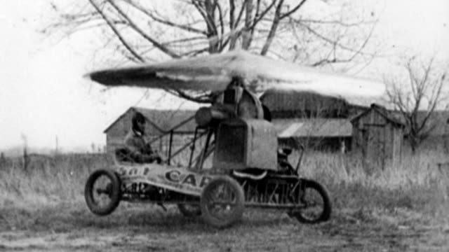 Man sitting in early helicopter invention 'Sky Car' / umbrella style wing makes the Sky Car bounce up and down on the ground Early failed flight...