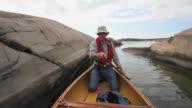 MS POV Man sitting in stern of canoe paddling rocky channel / Killarney, Ontario, Canada