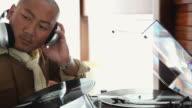 CU Man sitting next to record player listening to headphones / Palma de Mallorca, Mallorca, Baleares, Spain