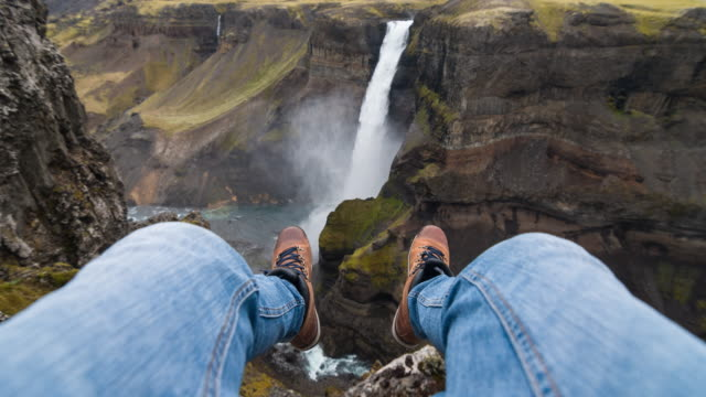 Man sitting on a cliff, looking at waterfall in canyon