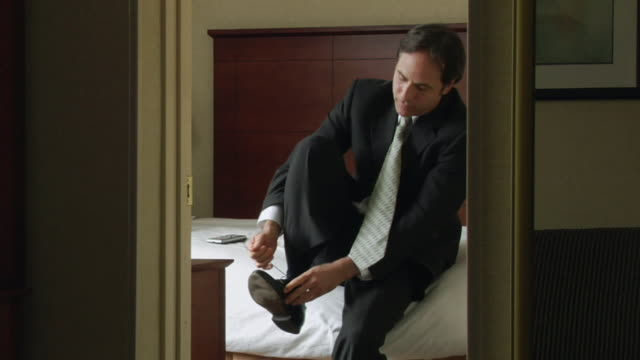 MS, Man sitting on bed in hotel room, putting on and tying shoes