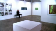 Man sitting on bench in gallery and talking on cell phone / standing up and walking away