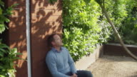 WS TD Man sitting on bench relaxing in garden / Eastbourne, Sussex, UK