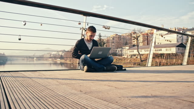 WS Man Sitting On Bridge And Using Laptop