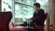 WS Man sitting on chair by window using laptop, drinking coffee / Whistler, British Columbia, Canada